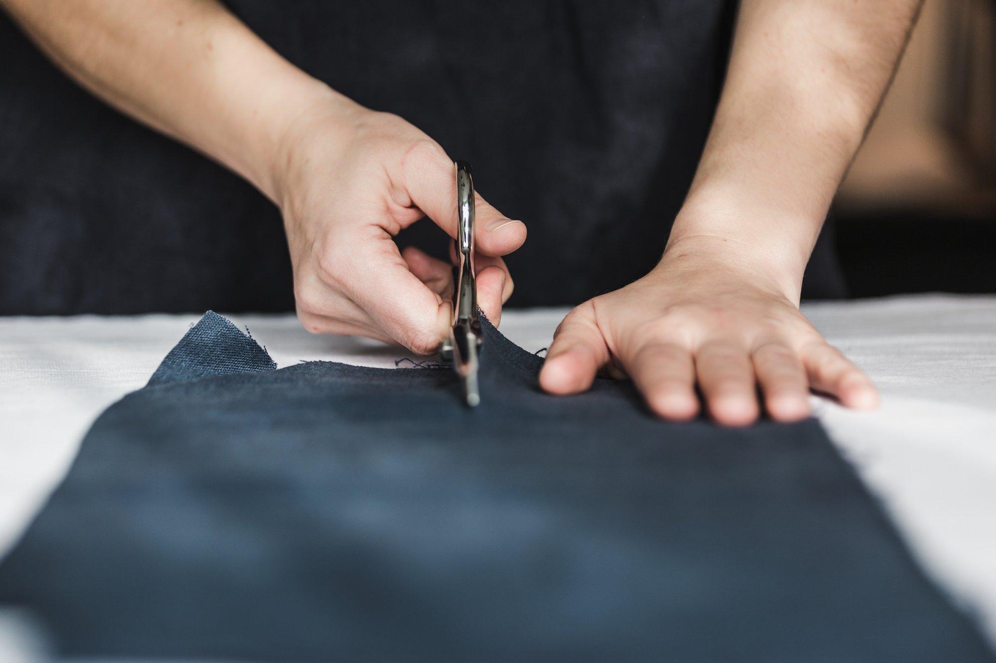 عکس پارچه لباس کار در حال برش